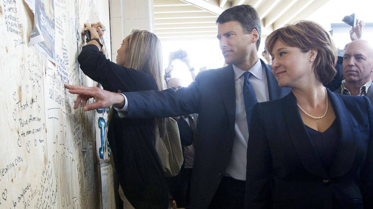 Vancouver Mayor Gregor Robertson and B.C. Premier Christy Clark look over messages of support on a board used to cover up a broken widow in Vancouver June 16, 2011.