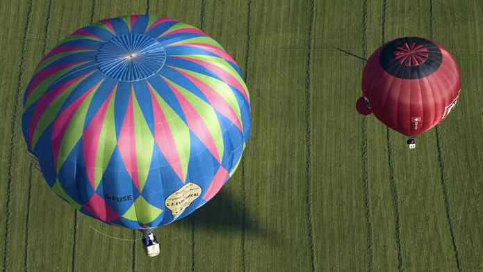 Two hot air balloons soar over a green meadow during a ballooning meeting in Kirchberg in the Austrian province of Tyrol, Friday, Sept. 23, 2011.