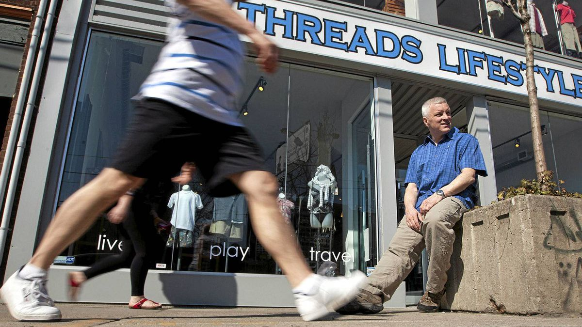 Steven Cross, the owner of Toronto outdoor apparel store Threads Lifestyle, sits outside his store on Wednesday, an unseasonably warm day.