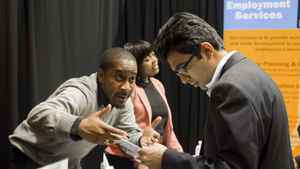 An exhibitor talks to a job seeker at the Bi-lingual Job Fair and Training Expo in Toronto on Thursday March 8, 2012 .