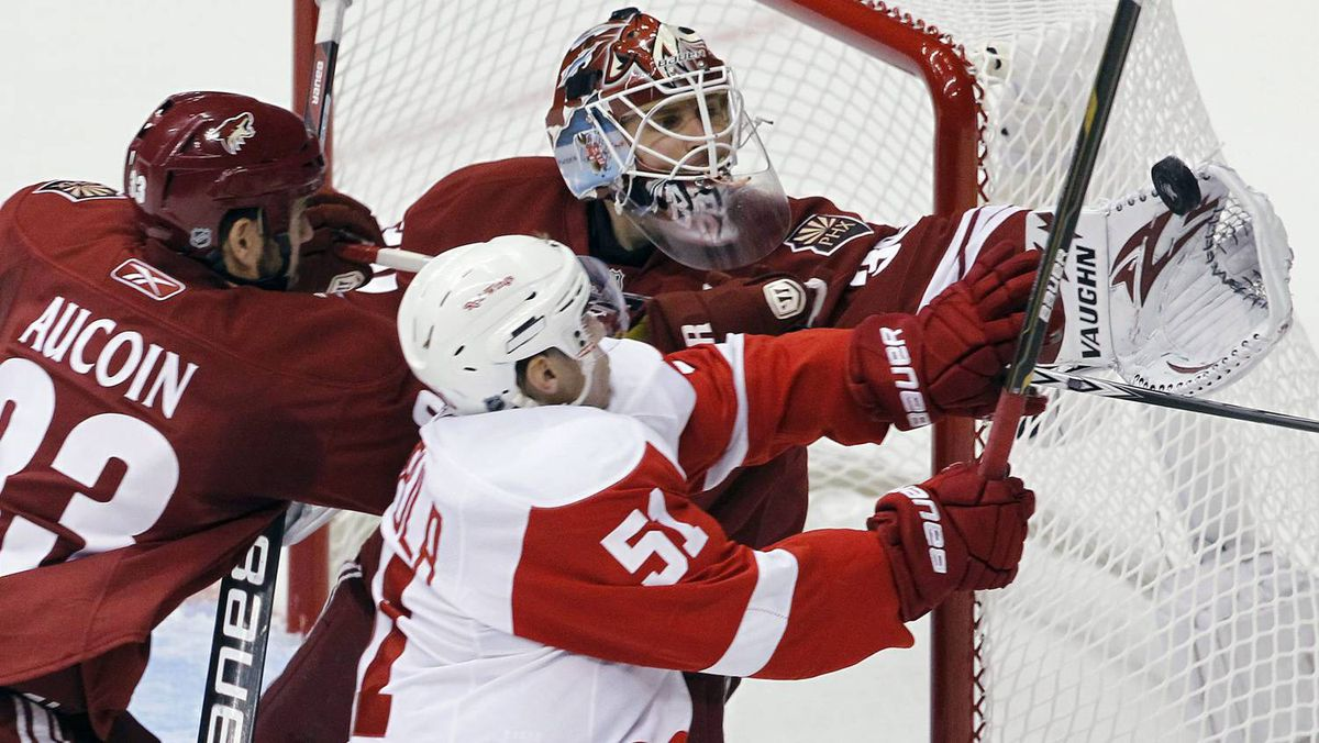 Phoenix Coyotes' Ilya Bryzgalov makes a glove save on a shot by Detroit Red Wings' Valtteri Filppula as Coyotes' Adrian Aucoin defends during the second period.