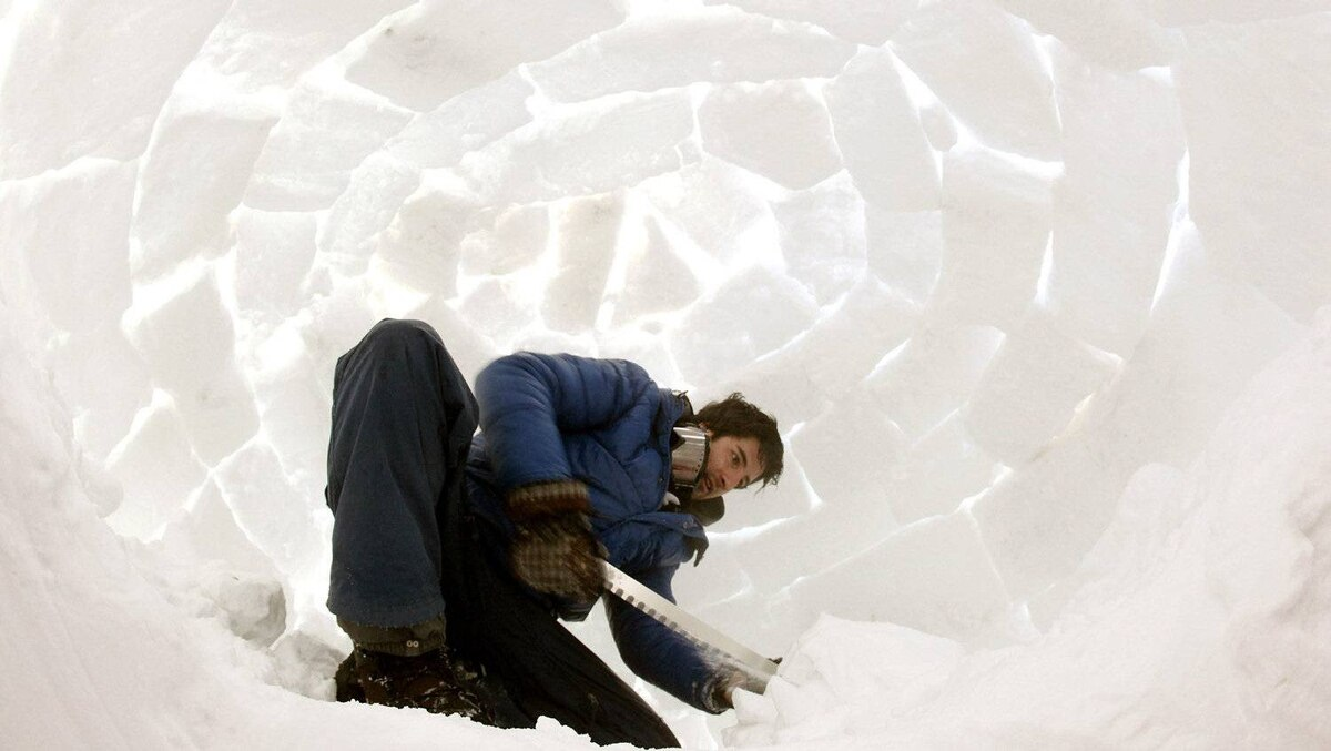 A member of the Occupy WEF movement uses a saw to cut blocks of snow for an igloo at their protest camp.