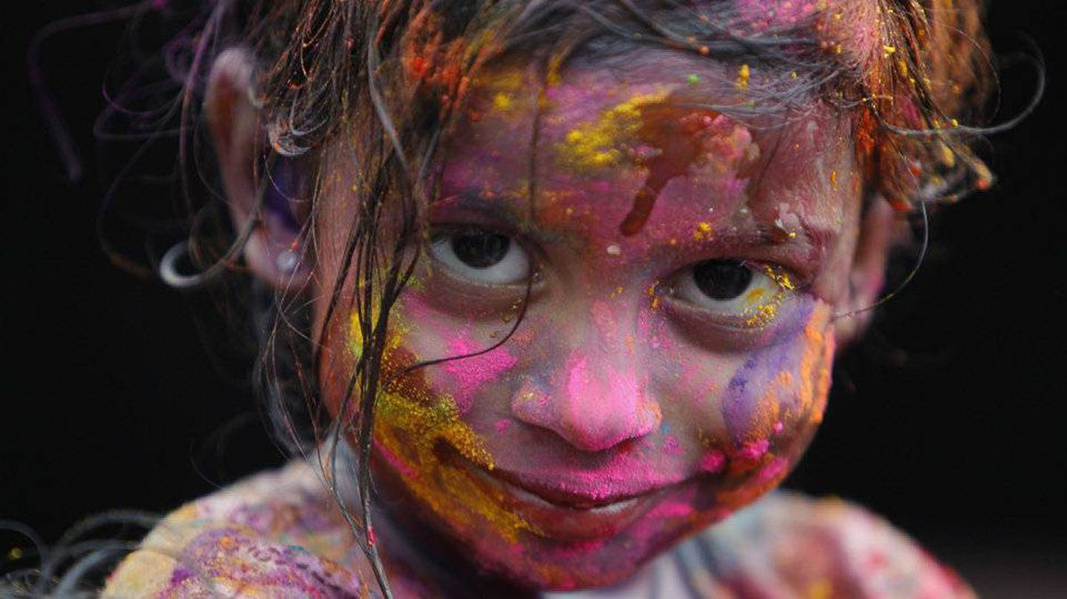 A girl smiles as her face is covered in coloured powder during Holi. The festival celebrates the death of the Demoness Holika, and the love between Lord Krishna and his beloved Radha.