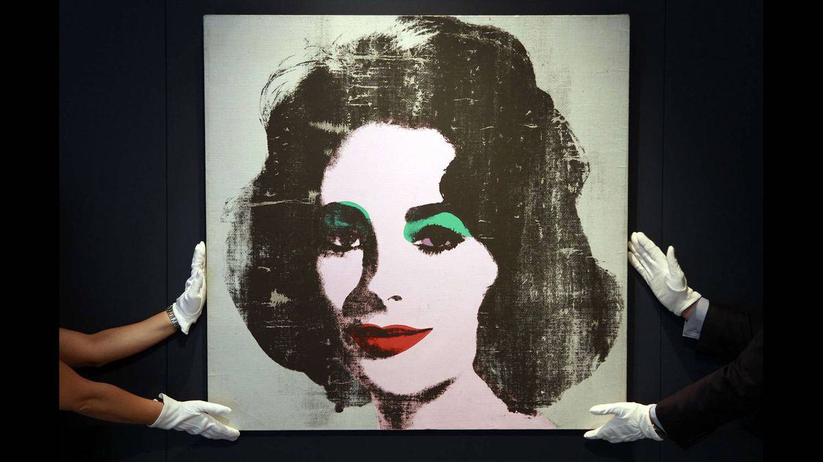"Employees pose for photographers with the 1963 ""Silver Liz"" portrait of actress Elizabeth Taylor by late artist Andy Warhol, unseen for more than 20 years, at Christie's auction house in London June 8, 2010."