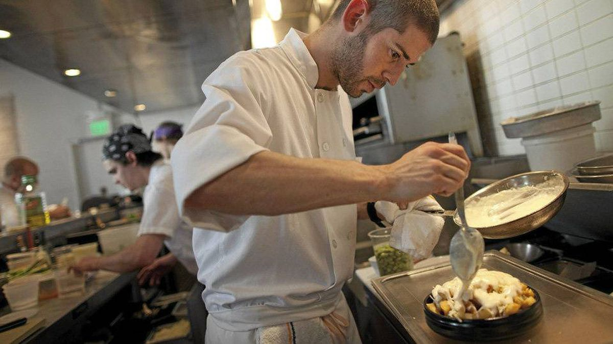 Sous chef Nick Adams puts on the finishing touches of a dish of Poutine at the Salt House Friday in San Francisco, California.