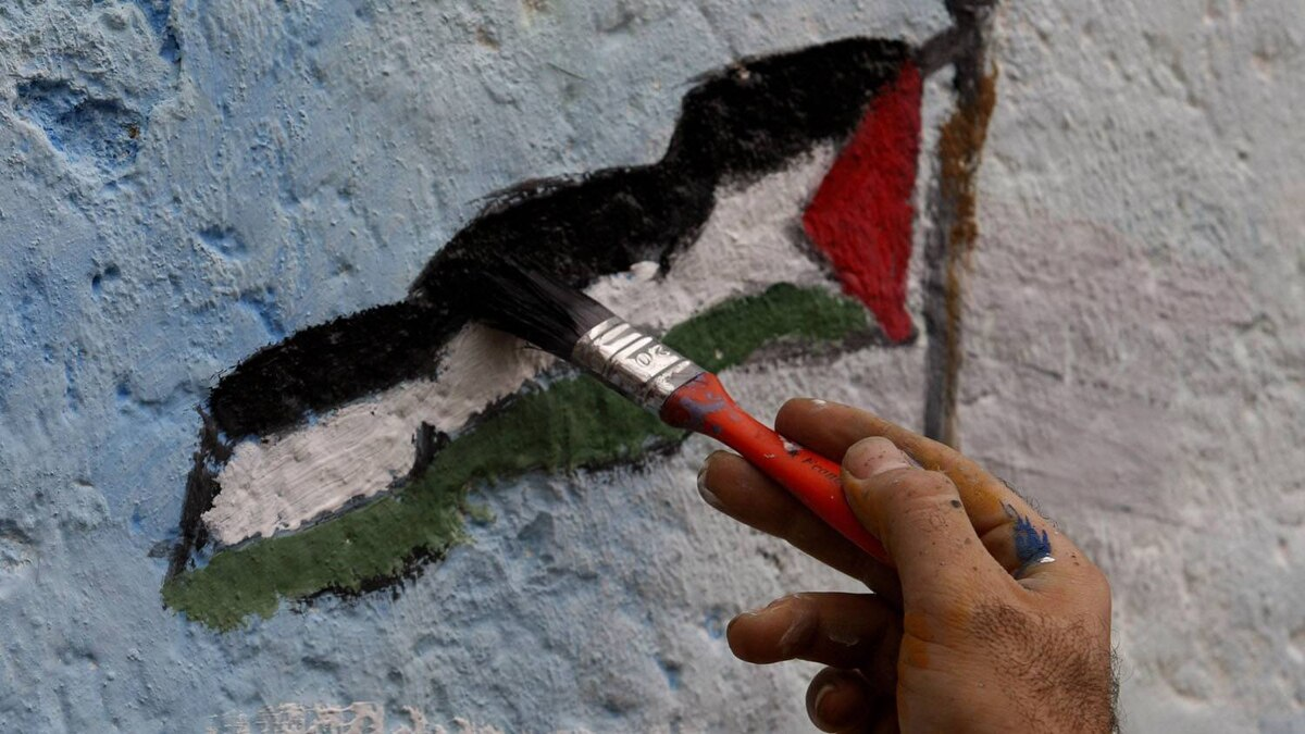 An artist paints a Palestinian flag, part of a larger mural in Jebaliya, northern Gaza Strip. Hatem Moussa/AP