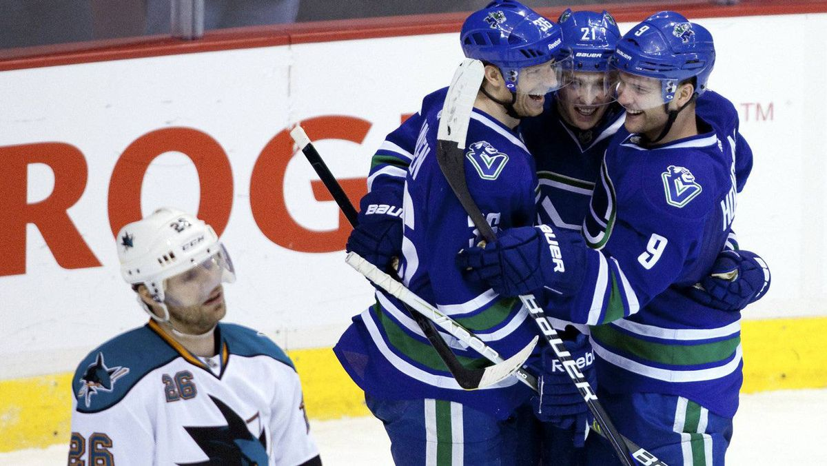 Vancouver Canucks Cody Hodgson (R) celebrates his second goal against the San Jose Sharks with teammates Jannik Hansen (36) and Mason Raymond in front of Sharks Michal Handzus during the third period of their NHL hockey game in Vancouver, British Columbia January 21, 2012.