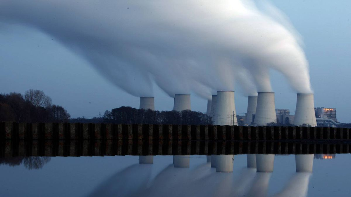 Steam billowing from the cooling towers of Vattenfall's Jaenschwalde brown coal power station is reflected in the water of a lake near Cottbus, eastern Germany