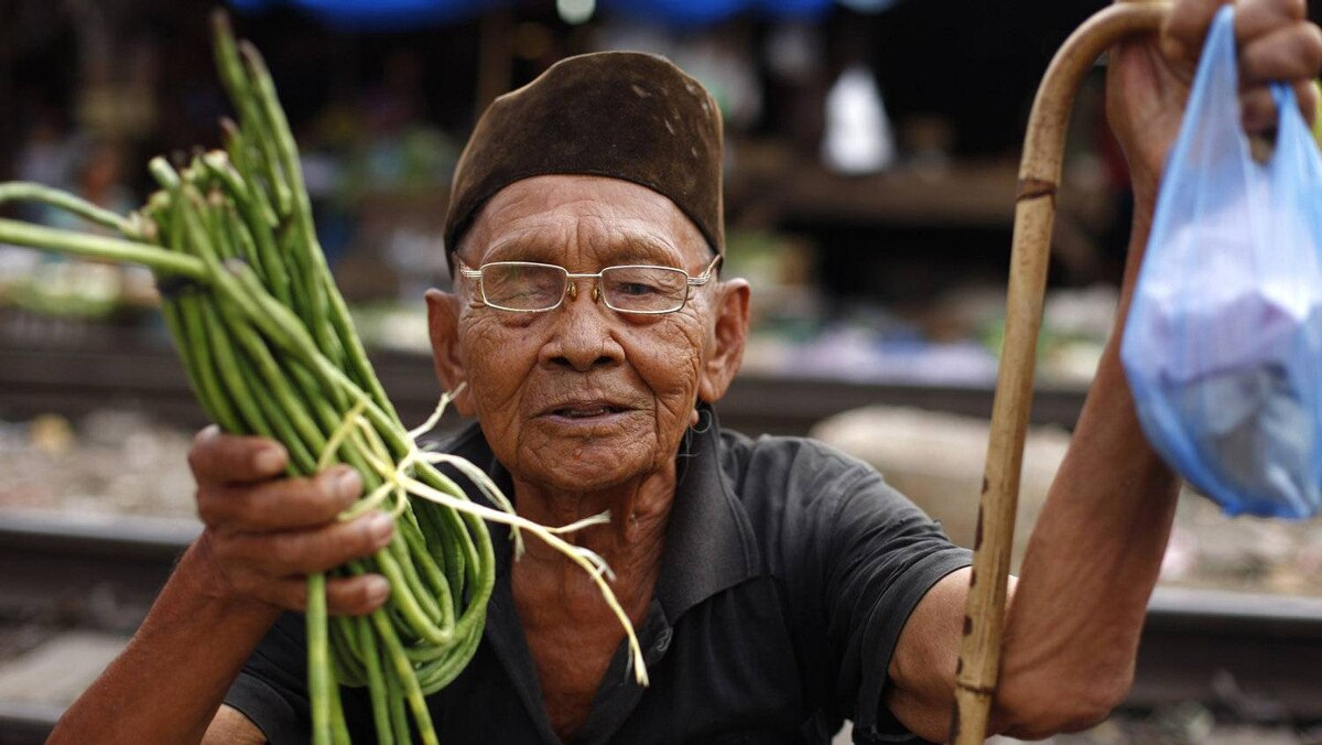 A man holds vegetables as he tries to bargain with the vendor at a market in Jakarta January 4, 2011. The Central Statistics Agency said on Monday that Indonesia's inflation for 2010 came in at 6.96 percent due to rising food prices.