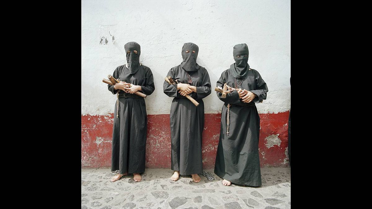 Valerie C. Burton photo: Women Penitents at Semana Santa Taxco, Mexico: People in Taxco make a vow to God and spend the week disguised in black clothing masks and chained together they walk bent over in processions to fulfill their vows