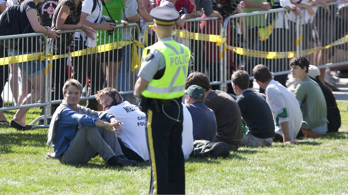 A police officer watches over protesters who had crossed the barricade to take part in a sit-in against the Keystone XL pipeline on the front lawn of Parliament Hill in Ottawa, Monday September 26, 2011.