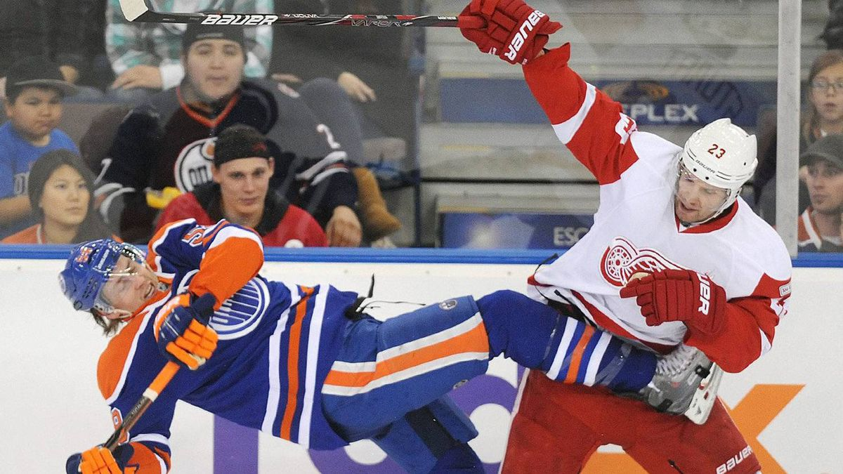 Detroit Red Wings Brad Stuart, right, checks Edmonton Oilers' Jeff Petry during second period NHL hockey action in Edmonton on Monday December 19, 2011. THE CANADIAN PRESS/John Ulan