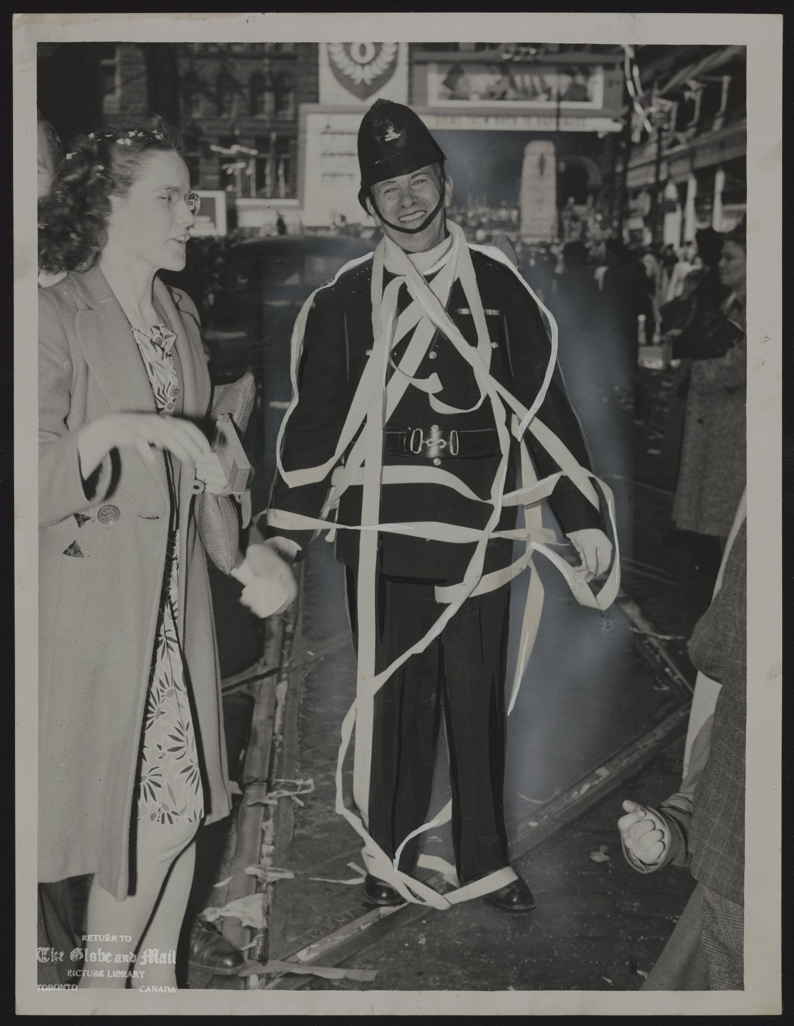 WORLD WAR II VE DAY PC HARRY CARROLL WAS FESTOONED WITH PAPER TAPE AS GAY THRONGS USED HIM FOR A MAYPOLE, HAD TO UNTANGLE HIMSELF SEVERAL TIMES AND RETIRE THRICE TO REMOVE LIPSTICK MARKS. [MAY 7, 1945 -- VICTORY IN EUROPE CELEBRATED IN TORONTO -- PC Harry Carroll was festooned with paper tape as gay throngs used him for a maypole, had to untangle himself several times and retire thrice to remove lipstick marks. Spontaneous celebratory parties and mass gatherings were held across the country on Monday, May 7, 1945 as the first