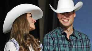 Prince William smiles at his wife Catherine, Duchess of Cambridge, during the Calgary Stampede on July 7, 2011.