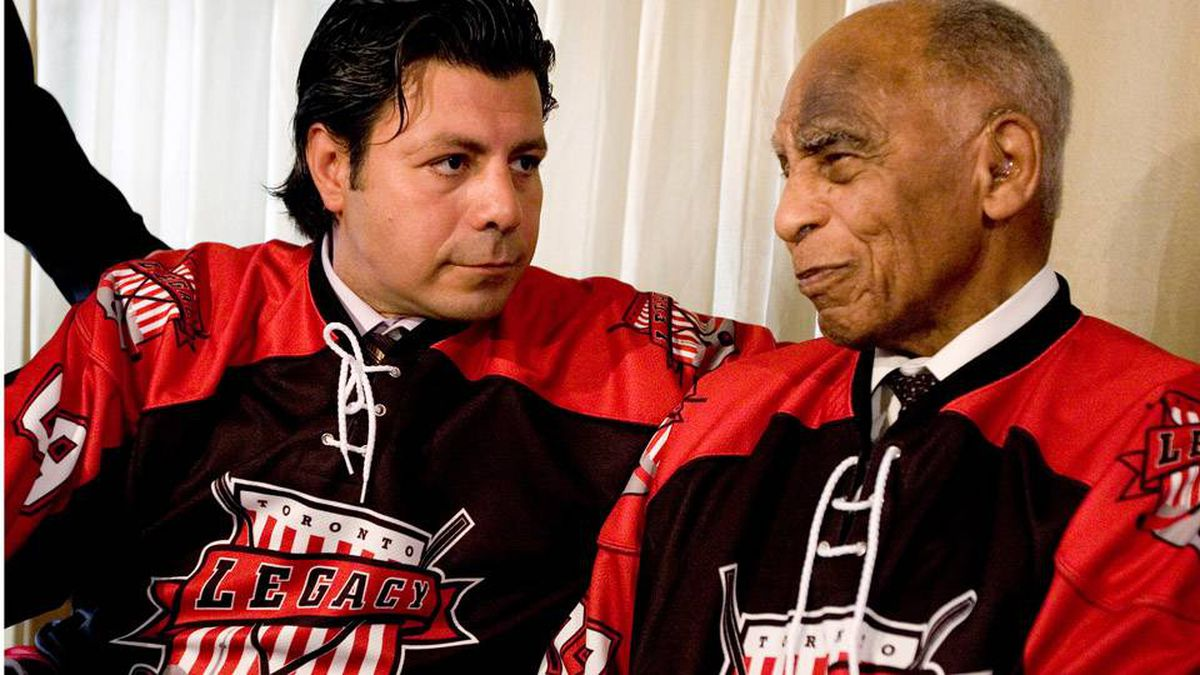 Andrew Lopez of the Toronto Legacy Group, left, and Order of Canada recipient Herb Carnegie don the jersey for the newly proposed NHL expansion team called the Toronto Legacy during a news conference on Friday.