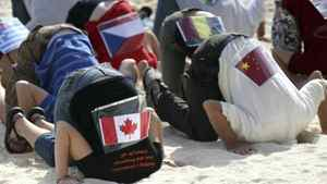 Sierra Club activists wearing flags, representing over 20 countries, take part in a protest by hiding their heads in the sand in the city of Cancun, Mexico Friday Dec. 3, 2010. The group was demonstrating their belief that countries participating in the United Nations Climate Change Conference, taking place in Cancun, are not doing enough to stop climate change.