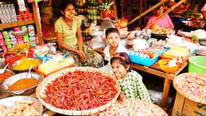 A family sells chilis, shallots, garlic and ginger at a market in Syriam town, just outside of Yangon. The ingredients form the base of many Burmese dishes.