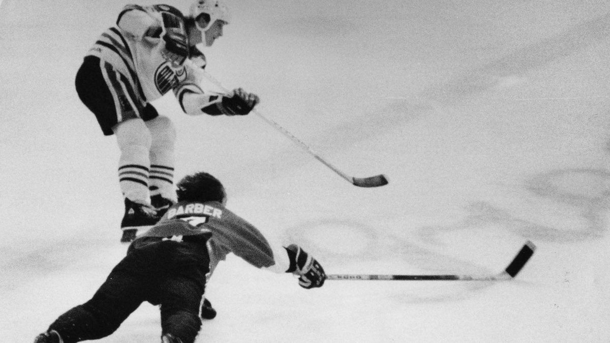 Edmonton Oiler's Wayne Gretzky is shown just after releasing the puck new the blue line for his 50th goal of teh seaon, in Edmonton, Dec. 30, 1981, as Piladelphia left winger Bill Barber dives. THE CANADIAN PRESS/Edmonton Journal- Bruce Edwards