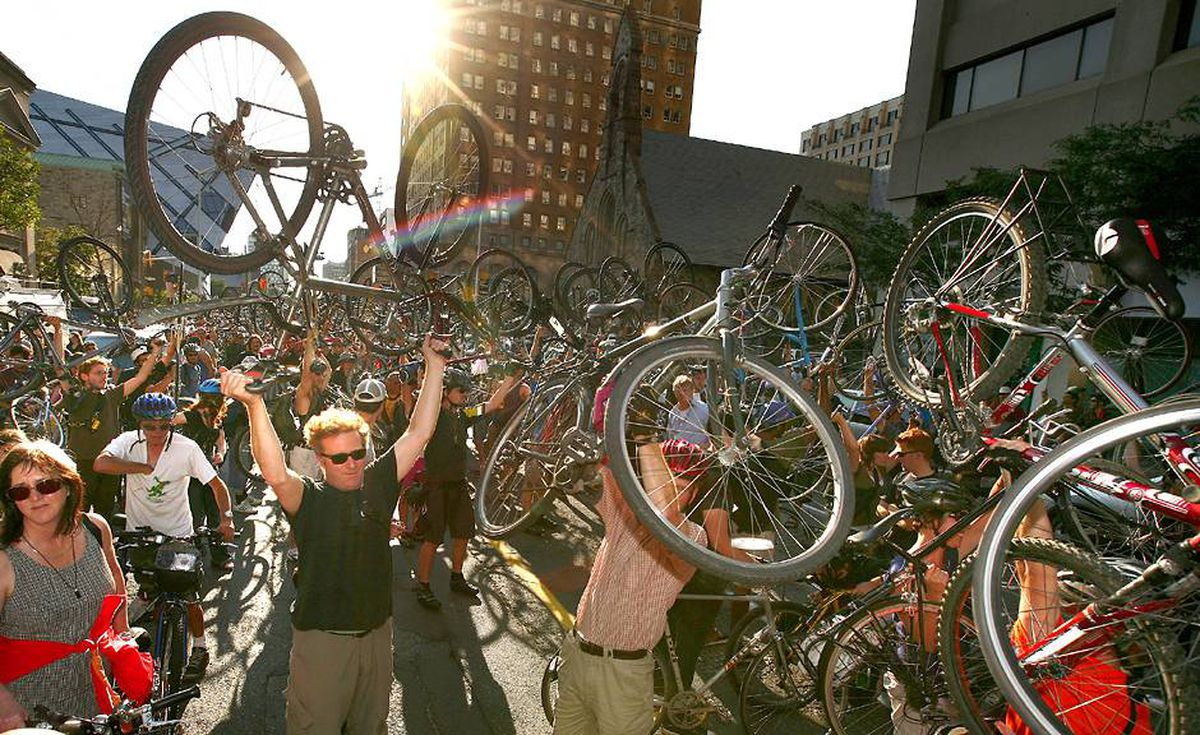 A groups of cyclists raise their bikes on Bloor Street in Toronto, in tribute to bike courier Darcy Allan Sheppard.