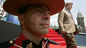 Prime Minister Stephen Harper walks past a mountie after addressing a crowd on Parliament Hill in Ottawa Saturday, July 1, 2006.