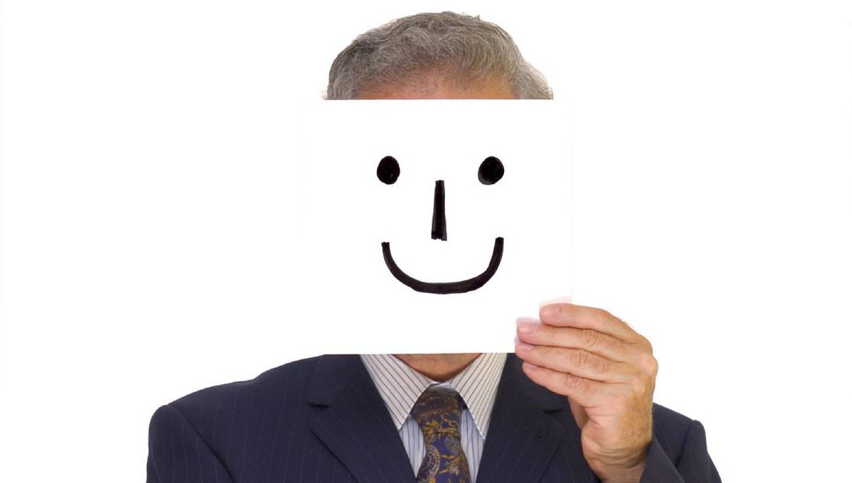 A pinstripe-suited businessman hold out his hand for a handshake with a home-made smiley mask in front of his face.