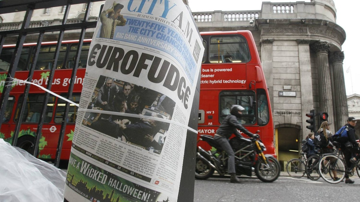 A financial newspaper is fixed to a pillar by a newspaper seller with The Bank of England building behind, in the city of London, Thursday, Oct. 27, 2011.