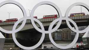 A barge with the Olympic rings floats below London Bridge as a line of double decker buses cross it during a promotional event on the Thames in London, February 28, 2012. Picture taken February 28, 2012. REUTERS