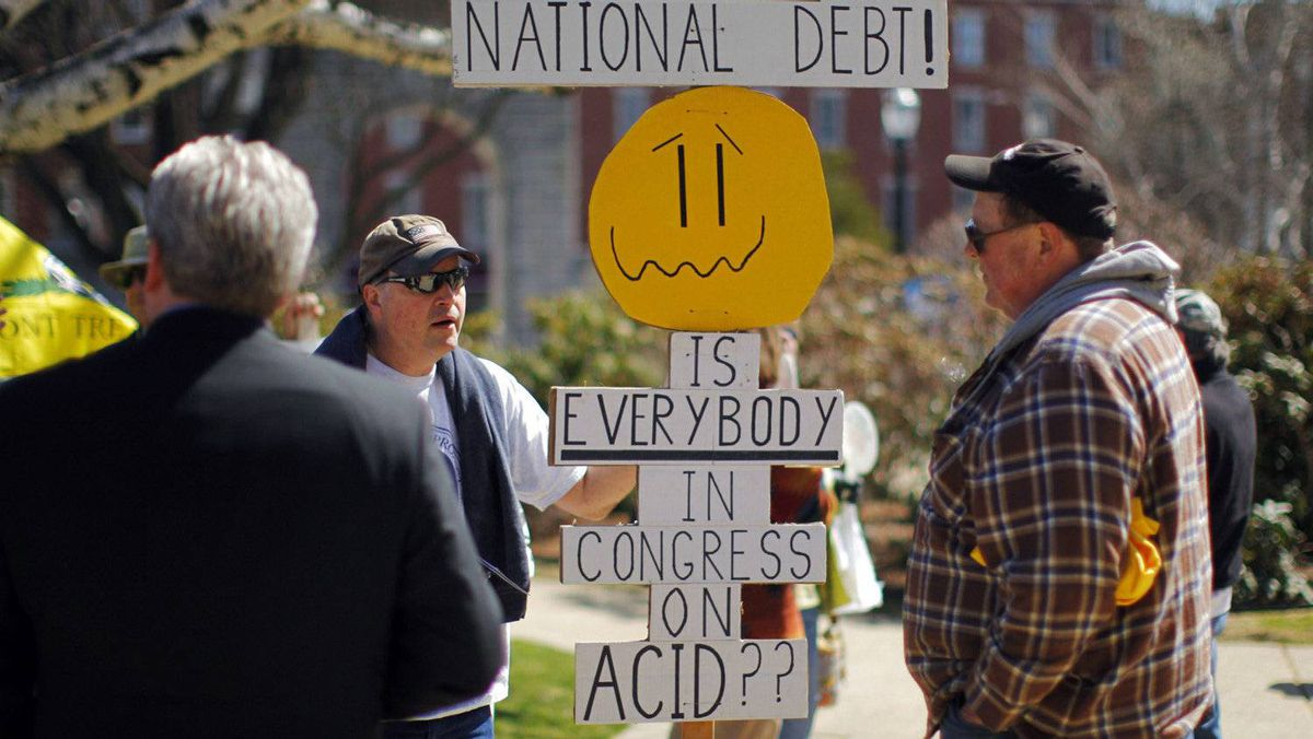 Voters, holding a sign referring to the U.S. national debt, wait for the start of the Tax Payer Tea Party Rally in Concord, N.H., April 15, 2011.