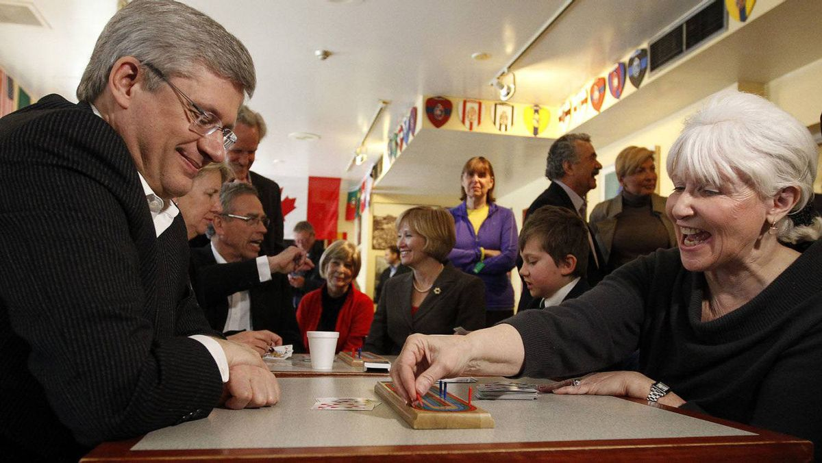 Conservative Leader Stephen Harper plays cribbage with Susan Collins during a campaign stop at a cultural centre in Toronto.