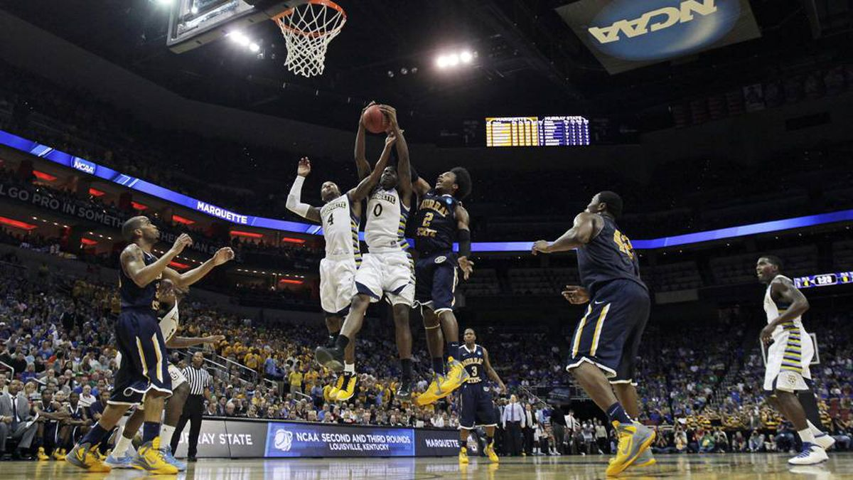 Marquette forward Jamil Wilson (0) fights for a rebound with teammate Marquette guard Todd Mayo (4) and Murray State forward Edward Daniel (2) in the second half of their NCAA third-round tournament college basketball game in Louisville, Ky., Saturday.
