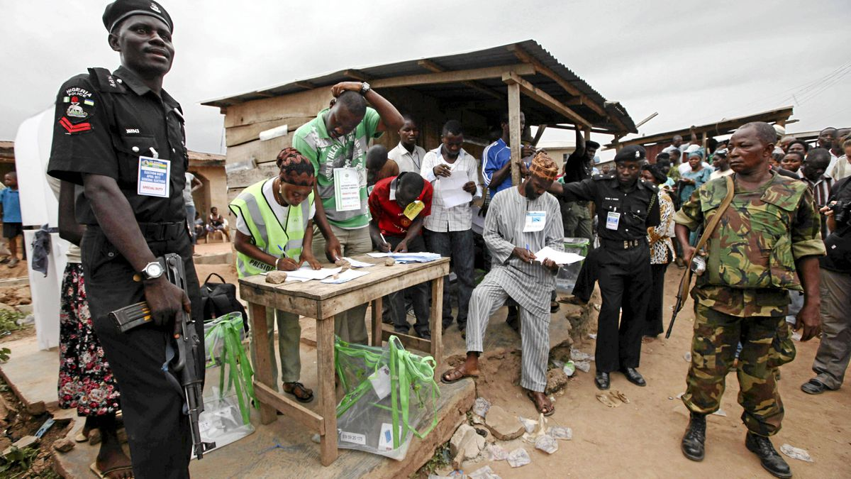 Soldiers of the Nigerian army, right, and a policeman, left, stand guard as electoral officials count ballot papers after the National Assembly election in Ibadan, Nigeria, April 9, 2011.