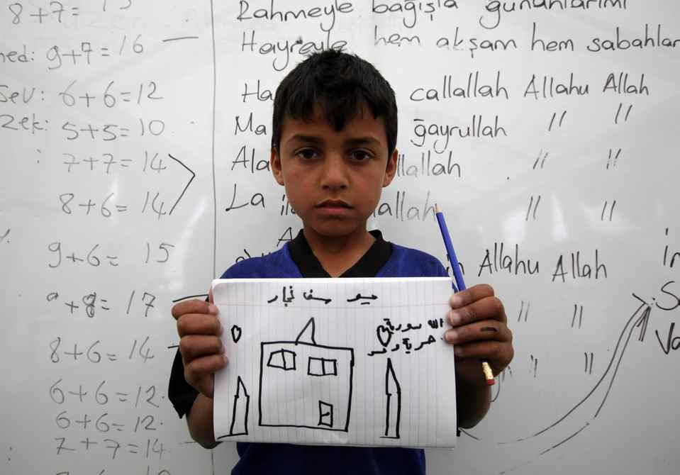 Yousuf Neccar, 10, a Syrian refugee, shows a drawing of his dream home during a class at a school for refugee children at Boynuyogun refugee camp in Hatay province near the Turkish-Syrian border.