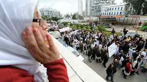 A woman watches from a balcony as Paramedical employees hold a strike in Algiers on Feb. 23, 2011.