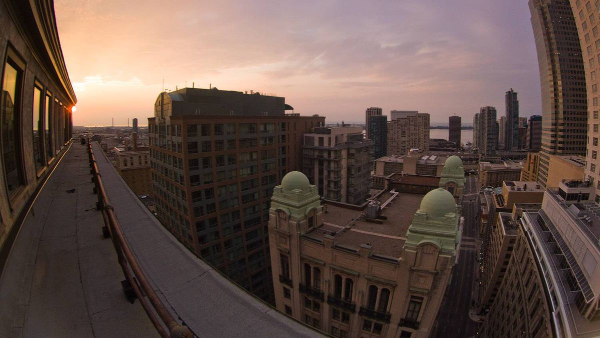 """Tom Ryaboi (tomms on Flickr) uploaded this image to our pool. He says: """"The sun rises over the financial district in Toronto. Shot just after 6 a.m., the super wide angle view was achieved through a fisheye lens."""" See more of his photos at www.blursurfing.com"""