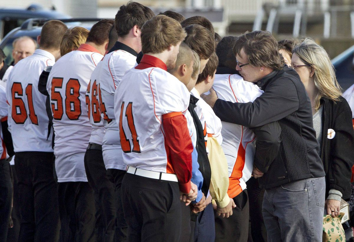 A mourner hugs football players wearing jersey's in honour Walter Borden-Wilkins during his funeral in Grand Prairie, Alberta on Thursday Oct. 27, 2011. Borden-Wilkins, 15, was killed in a car accident along with Matt Deller, 16, Tanner Hildebrand, 15 and Vincent Stover, 16, in Grande Prairie on Saturday.