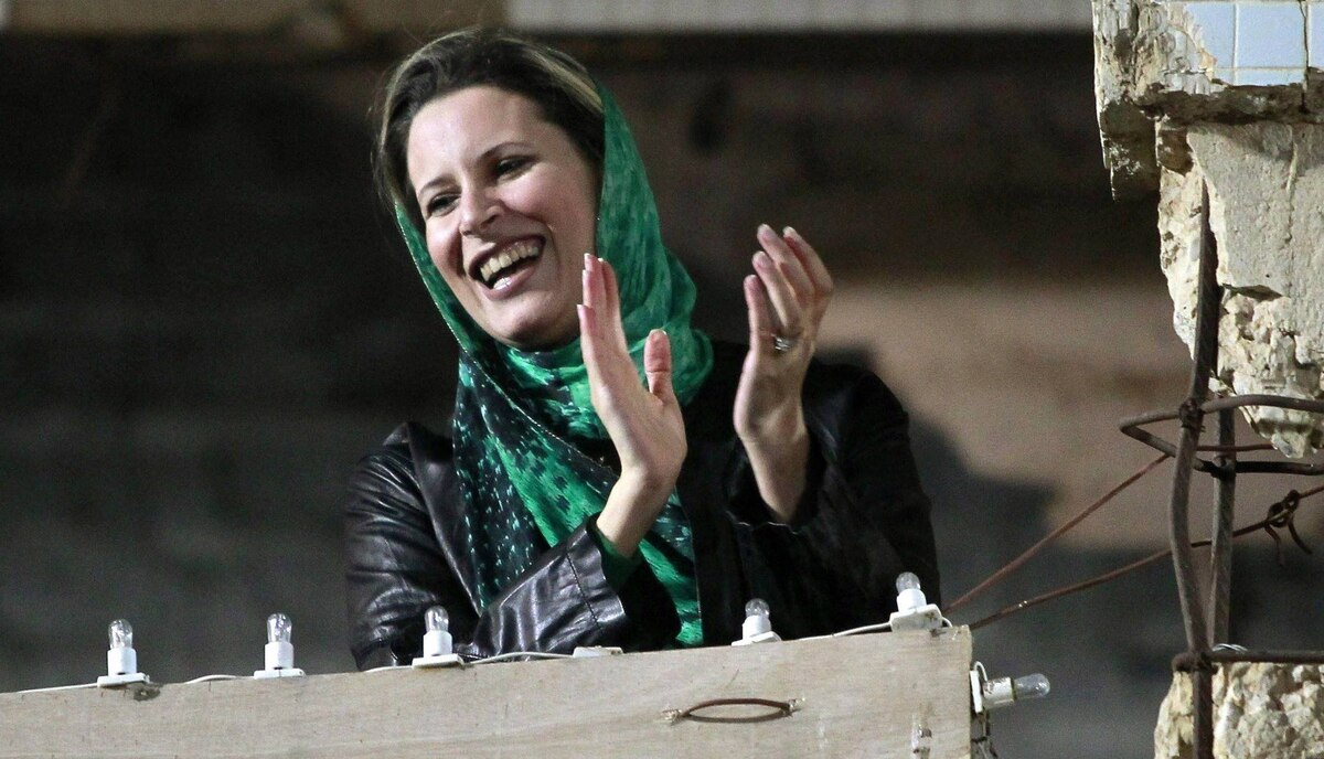 Aisha Gadhafi, daughter of Libya's former leader Moammar Gadhafi, claps during a pro-government rally at the heavily fortified Bab al-Aziziya compound in Tripoli in this April 14, 2011 file photo. A pregnant Aisha al-Gadhafi, fled to Algeria with other members of the family shortly after rebels took control of Tripoli. Algerian authorities reported that she gave birth to a baby girl soon after she arrived. Aisha made headlines in 2004 after she joined a team of lawyers defending former Iraqi leader Saddam Hussein.