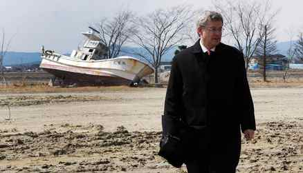 Prime Minister Stephen Harper visits the coastal region of Sendai, Japan, on Monday, March 26, 2012. The area was heavily impacted by the March 11, 2011, earthquake and tsunami. A boat that was washed 1 km inland is seen in the background.