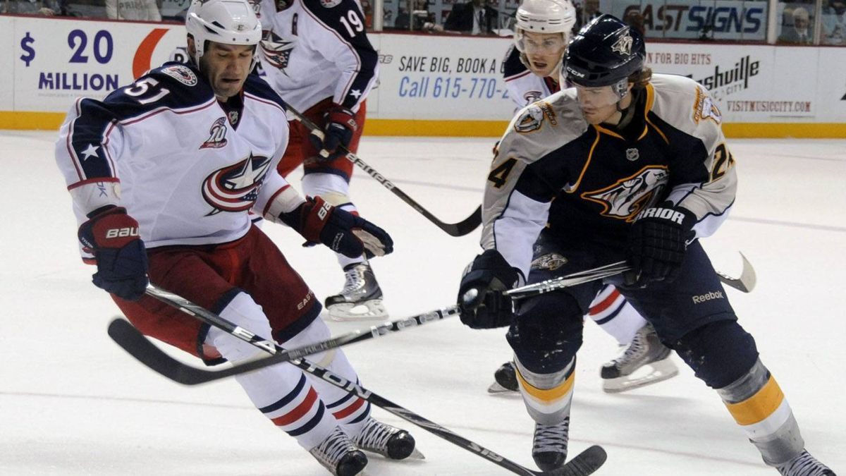 Columbus Blue Jackets defenseman Fedor Tyutin (51), of Russia, and Nashville Predators' forward Matt Halischuk (24) try to control the puck during the first period of an NHL hockey game Sunday, Feb. 27, 2011, in Nashville, Tenn. The Predators won 3-2. (AP Photo/Mike Strasinger)