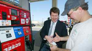 Federal Director of the Canadian Taxpayers Federation, John Williamson, left, shakes hands with Francis Morissette, right, of Fredericton, New Brunswick, at a gas station in Fredericton, Wednesday, May 14, 2008. Williamson gave Morissette $29, the percentage of tax Morissette would have paid for his $100 tank of gas.