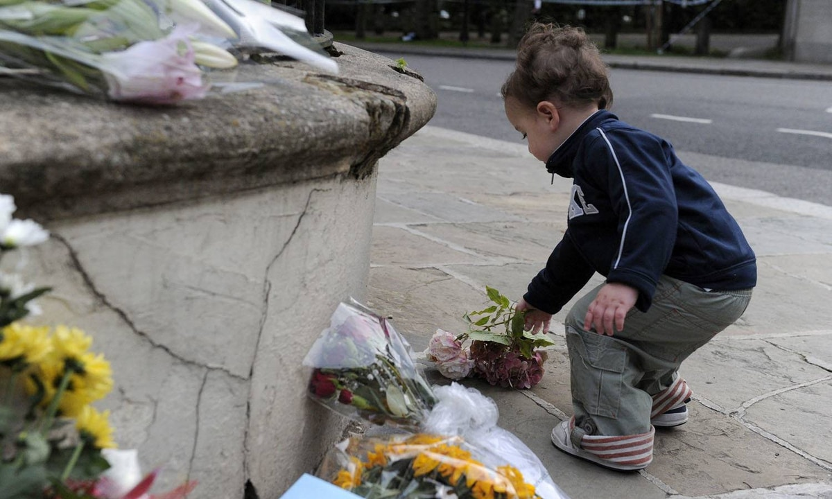 A boy lays flowers near the house in north London where the body of Amy Winehouse was found on July 23 2011.
