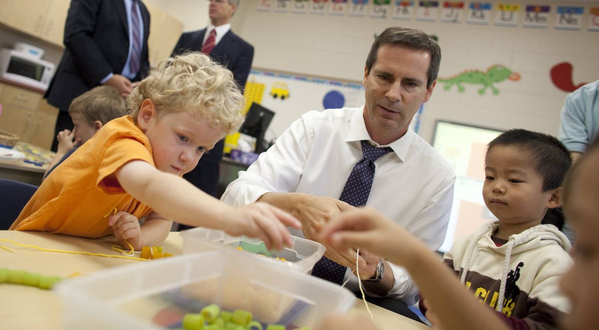 Ontario Premier Dalton McGuinty builds necklaces with Nathan Skinner, 3, left, and Alex You, 4, in a full-day kindergarten class at Stoney Creek Public School in London on Oct.8, 2010.