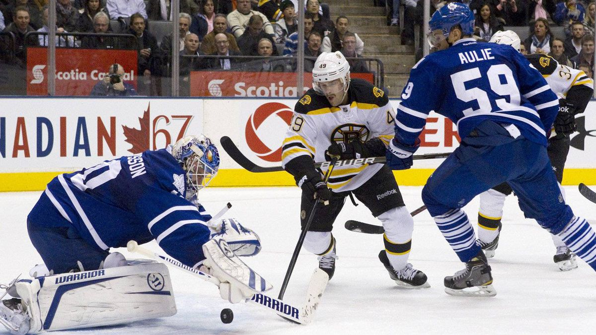 Toronto Maple Leafs goaltender Jonas Gustavsson (left) drops onto the puck in front of Boston Bruins Rich Peverley (centre)as Leafs' Keith Aule looks on during first period NHL hockey action in Toronto on Wednesday November 30, 2011.
