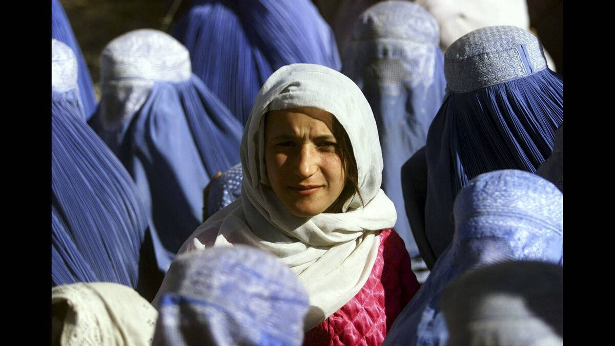 A young Afghan woman shows her face in public for the first time after 5 years of Taliban Sharia law as she waits at a food distribution centre in central Kabul, November 14, 2001.