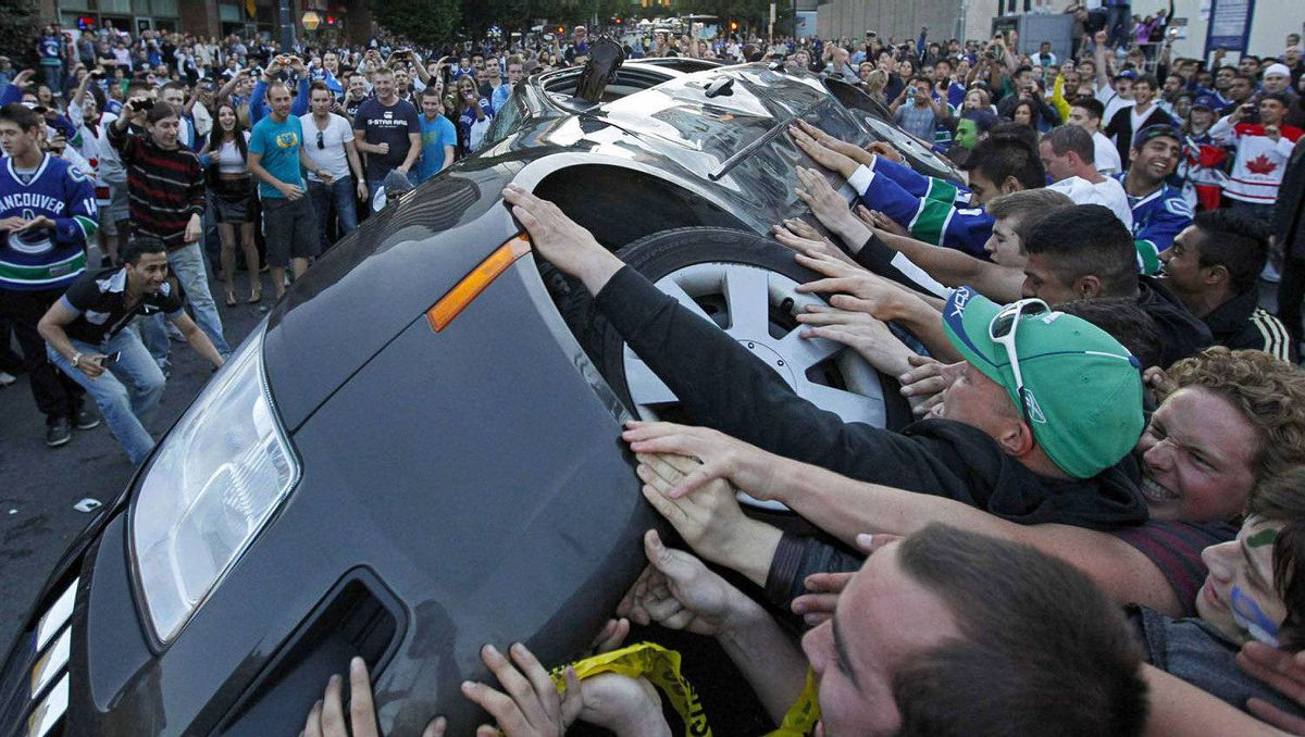 People push over a vehicle in Vancouver after the Canucks lost Game 7 of the Stanley Cup Final to the Boston Bruins.
