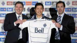 Newly-signed Vancouver Whitecaps FC player Young-Pyo Lee, centre, poses for a photo with team head coach Martin Rennie, right, and team president Bob Lenarduzzi news conference at B.C. Place in Vancouver, B.C. Sunday, Dec, 7, 2011. The team announced Wednesday that they had signed Lee of South Korea to the team.