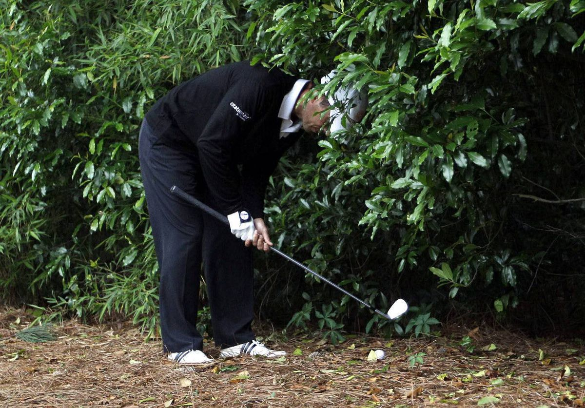 Mike Weir hits from the bushes off the sixth fairway during the second round of the Masters golf tournament in Augusta, Ga.