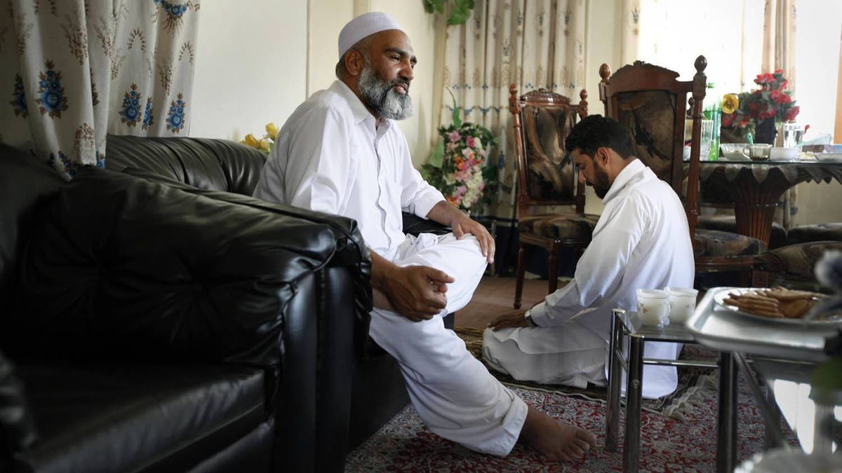 Saqib Jadoon, 46, co-owner of Dawn Builders, one of the largest construction firms in Abbottabad, Pakistan, speaks to The Globe and Mail as a colleague prays in the background on May 4, 2011.