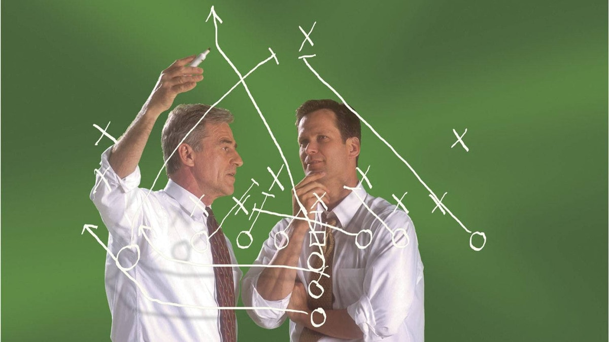 Businessmen discussing diagram of a football play.