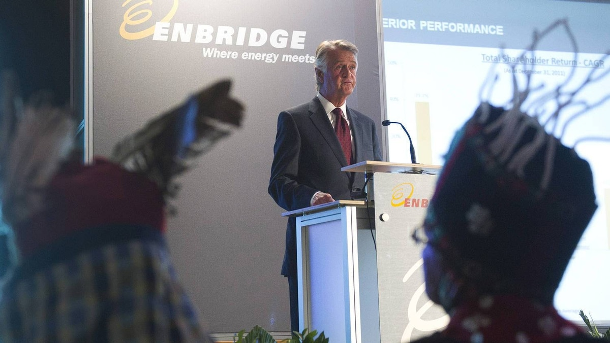 Inside the hotel, Enbridge Inc. president and CEO Patrick Daniel speaks at the annual meeting as John Ridsdale, Chief Na'Moks, of the Wet'suwet'en First Nation, right, and Chief Martin Louie of Nadleh Whut'en nation, left, listen.
