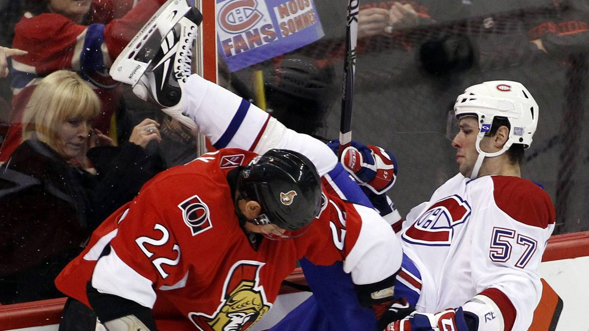 Ottawa Senators' Chris Kelly (L) hits Montreal Canadiens' Benoit Pouliot during the first period of their NHL hockey game in Ottawa October 23, 2010.